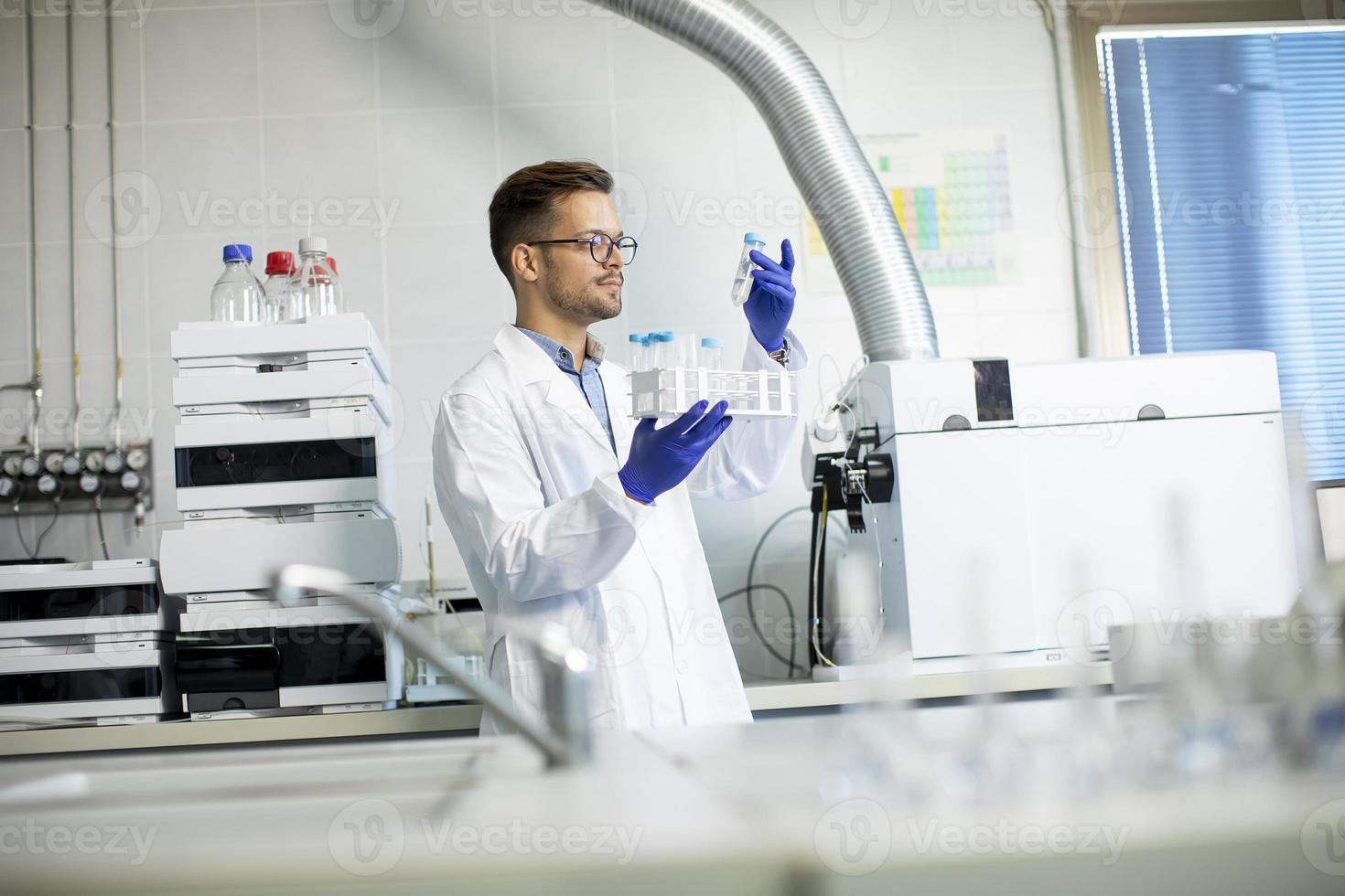 ung forskare som arbetar med kemiska prover i laboratorium med hplc-system och kromatografiutrustning foto