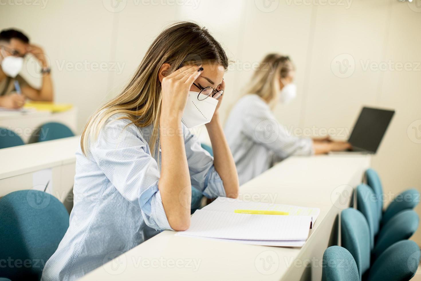 kvinnlig student som bär ansiktsskyddande medicinsk mask för virusskydd vid föreläsningssalen foto
