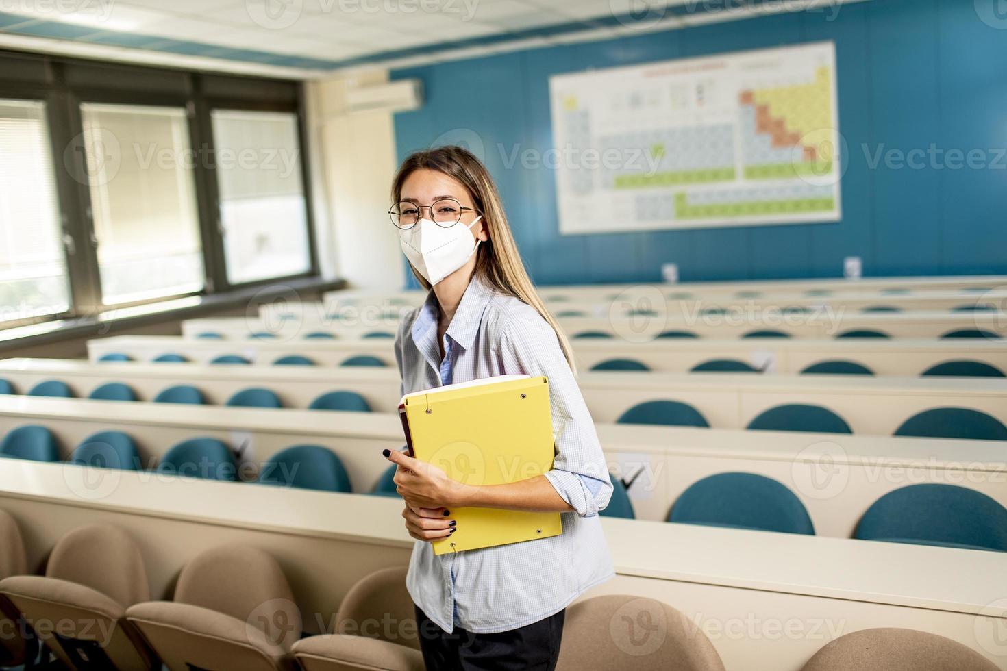kvinnlig student som bär ansiktsskyddande medicinsk mask för virusskydd som står vid föreläsningssalen foto