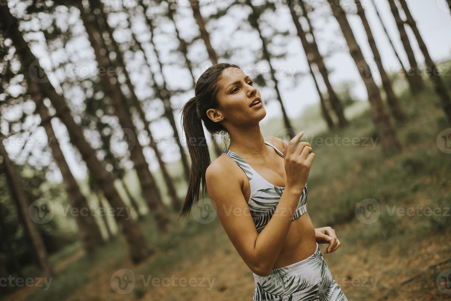ung fitness kvinna kör på skogsstig foto