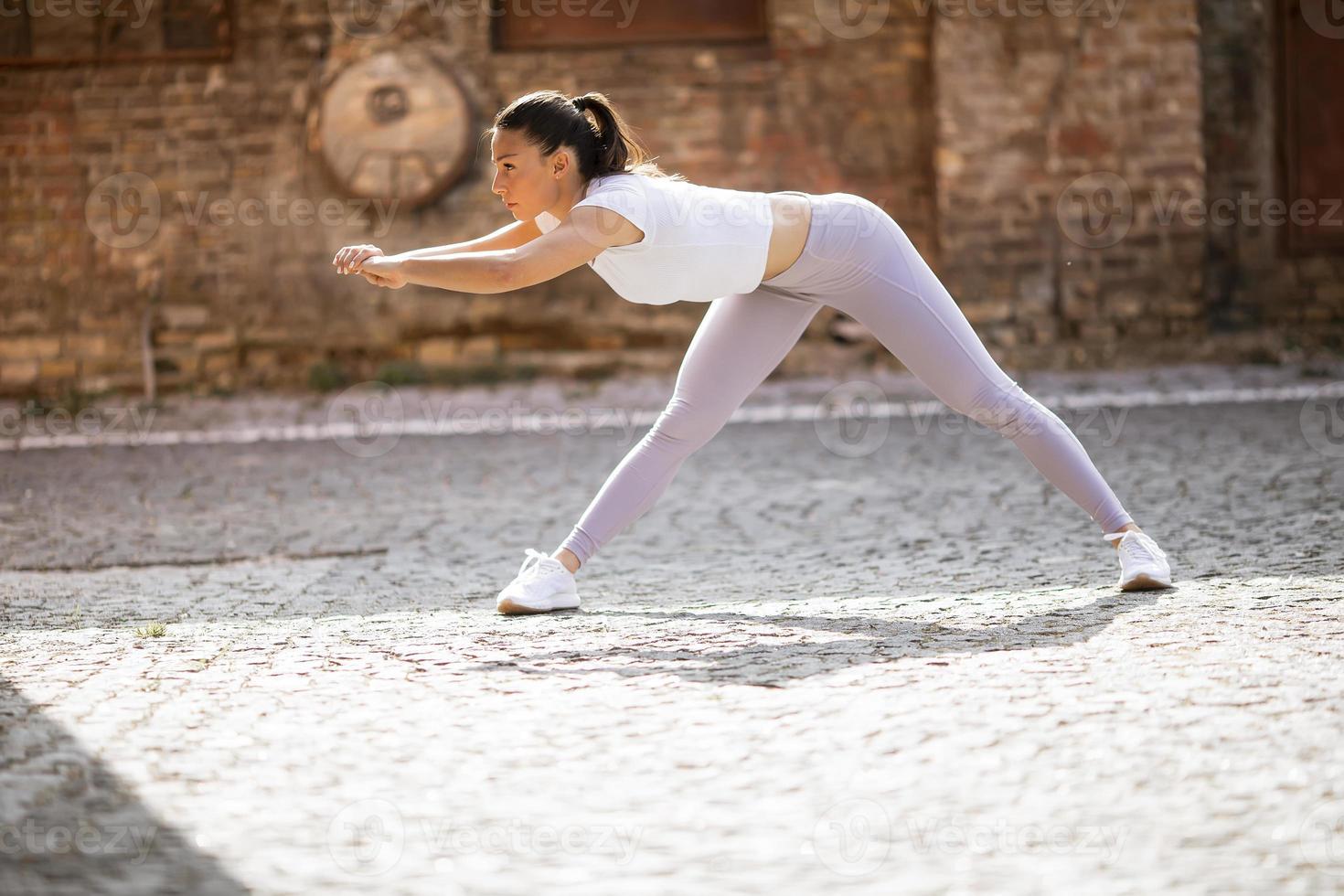ung kvinna som sträcker sig under träning i stadsmiljön foto