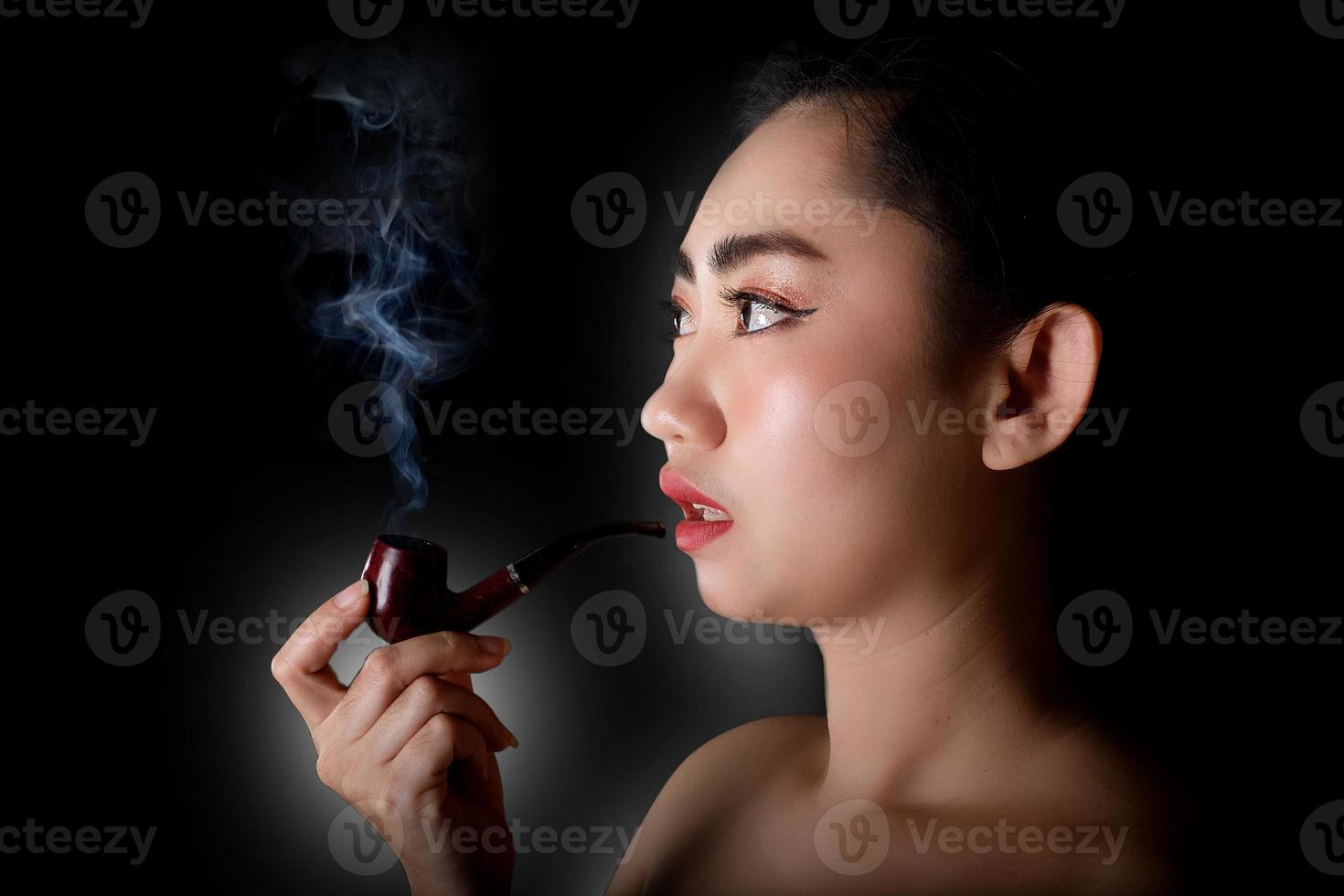 kvinna som röker en piptobak på svart bakgrund foto
