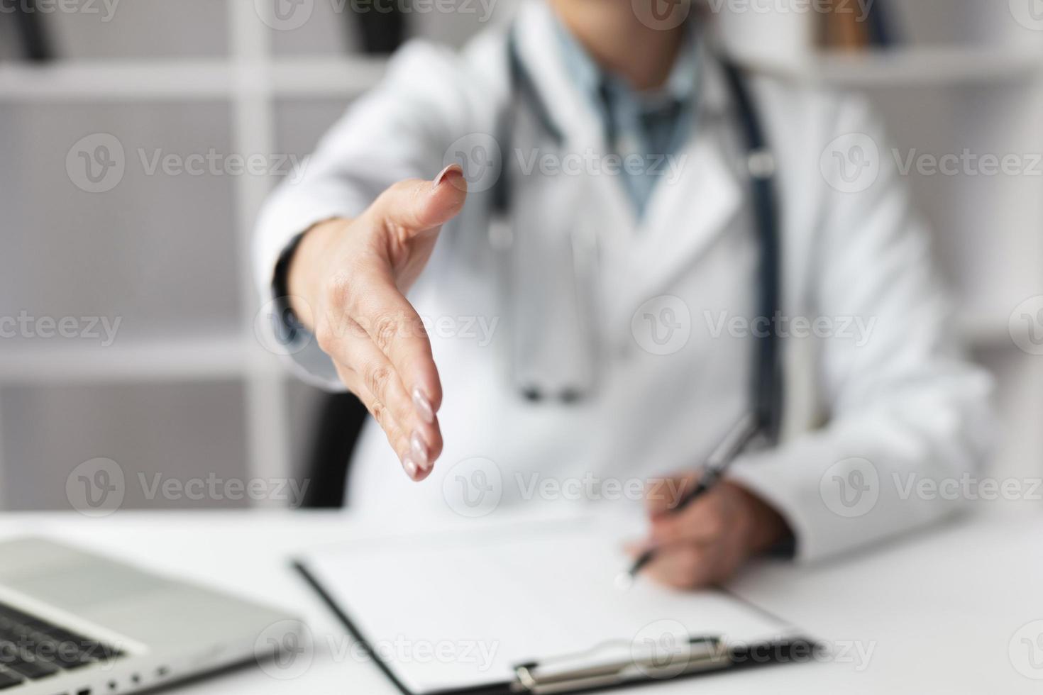 närbildläkare som väntar på att skaka patientens hand foto