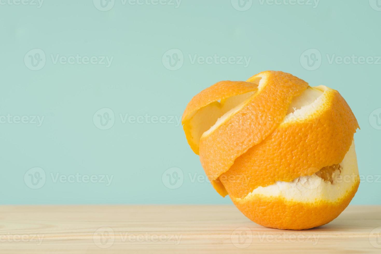 närbild skalad orange frukt på träytan foto