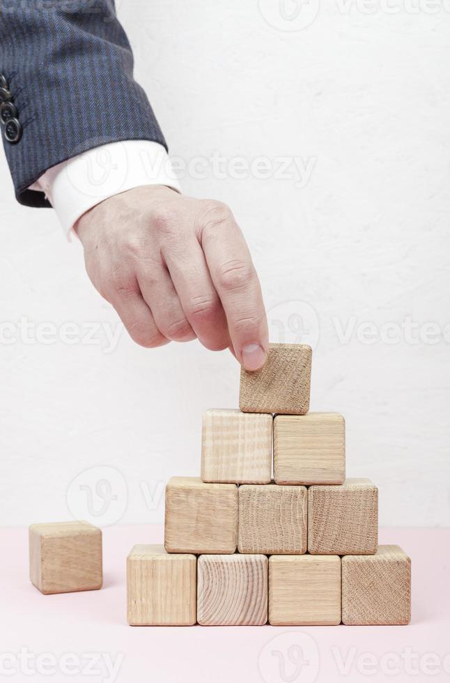 hand som skapar pyramid från träkuber på vit bakgrund foto