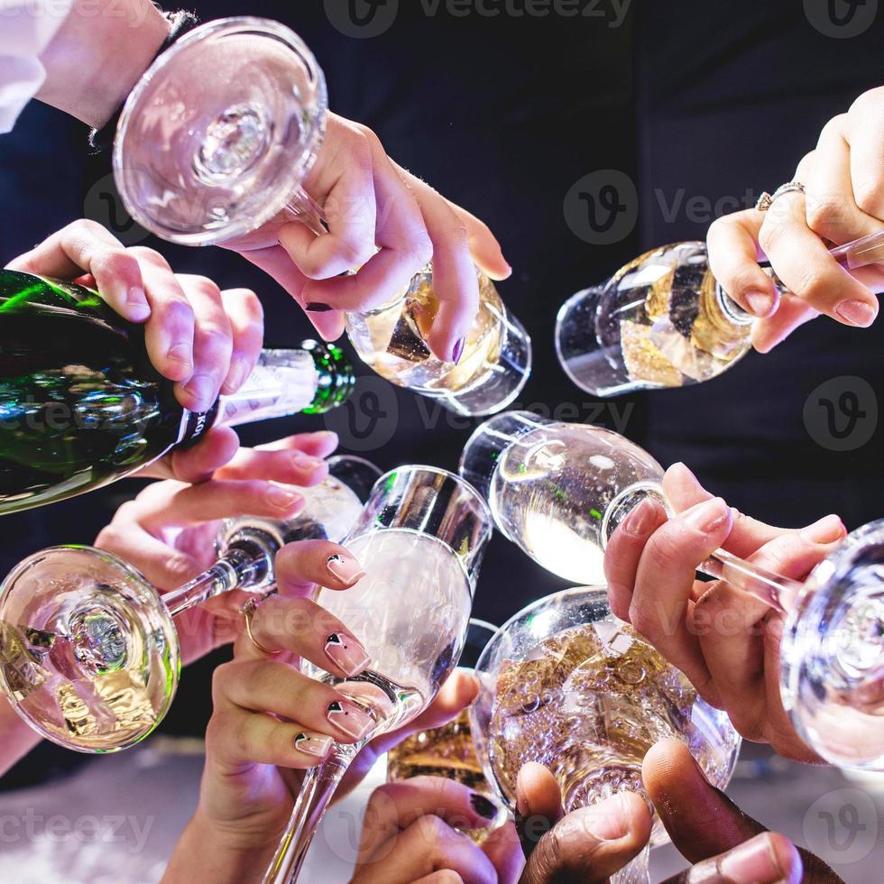 händer av vänner med vinglas i firandet foto
