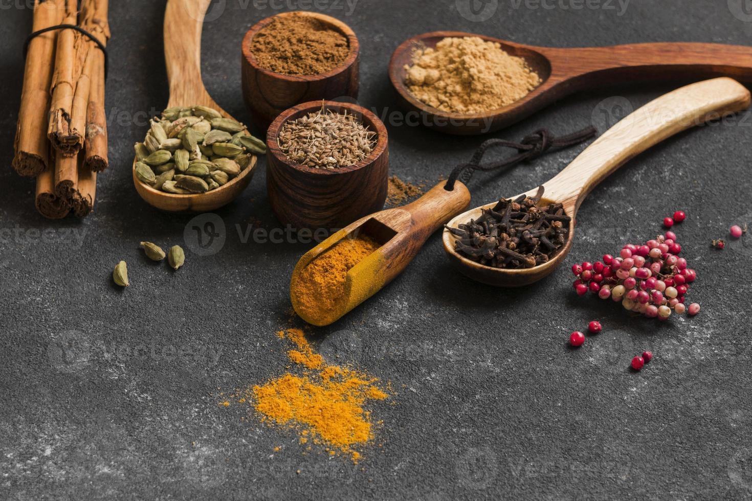 högvinklade träskedar med kryddor foto