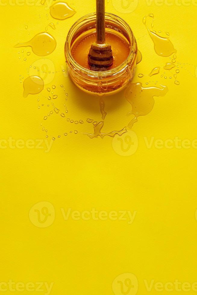 burk med honung på gult bord med kopieringsutrymme foto