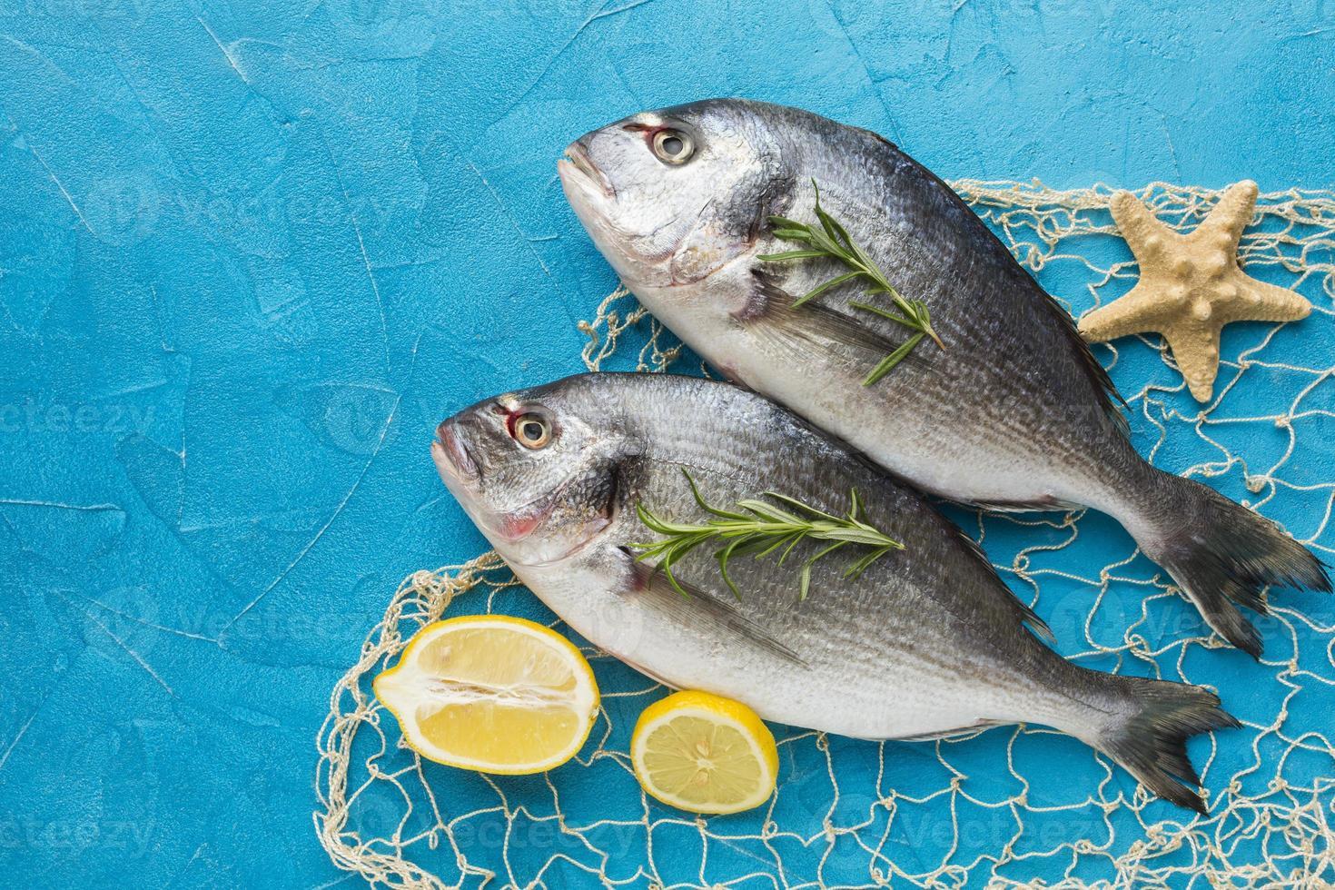 fiskarrangemang med citron på blå bakgrund, ovanifrån foto