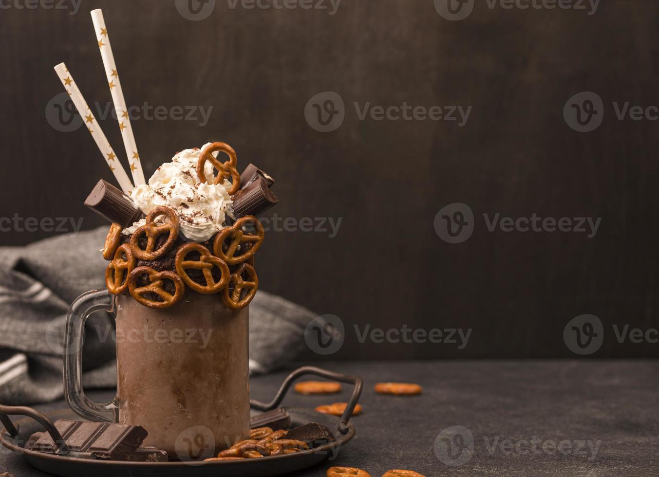 framifrån choklad milkshake med sugrör kringlor foto