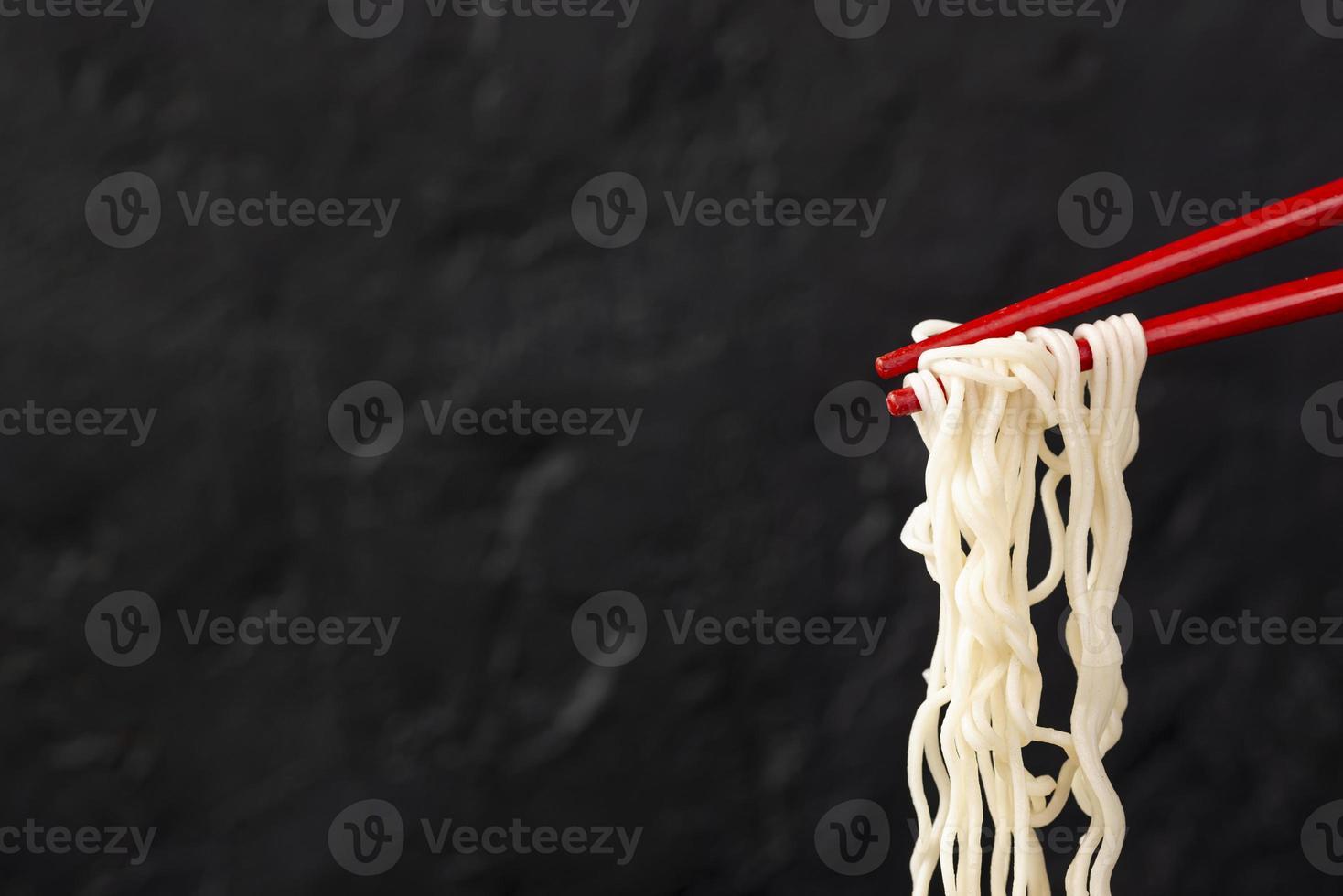 framsiktsnudlar på ätpinnar med kopieringsutrymme på svart bakgrund foto
