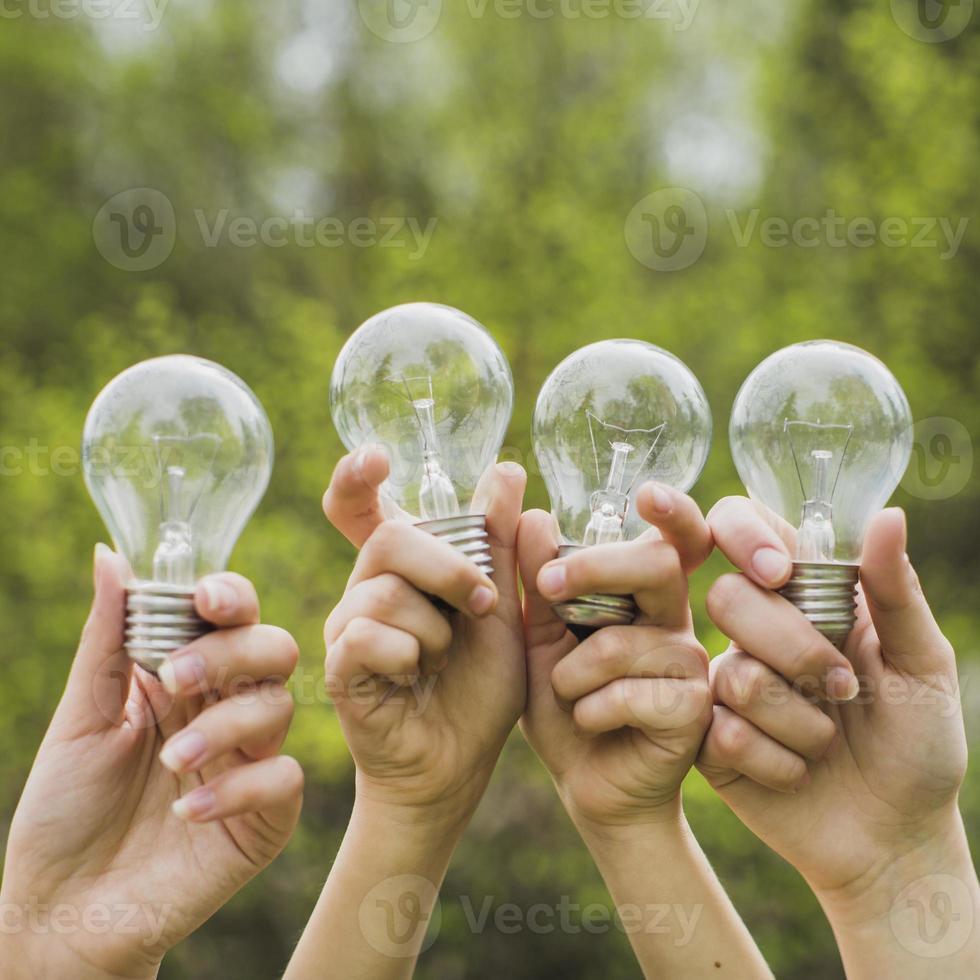 händer som håller glödlampor i luften i naturen foto