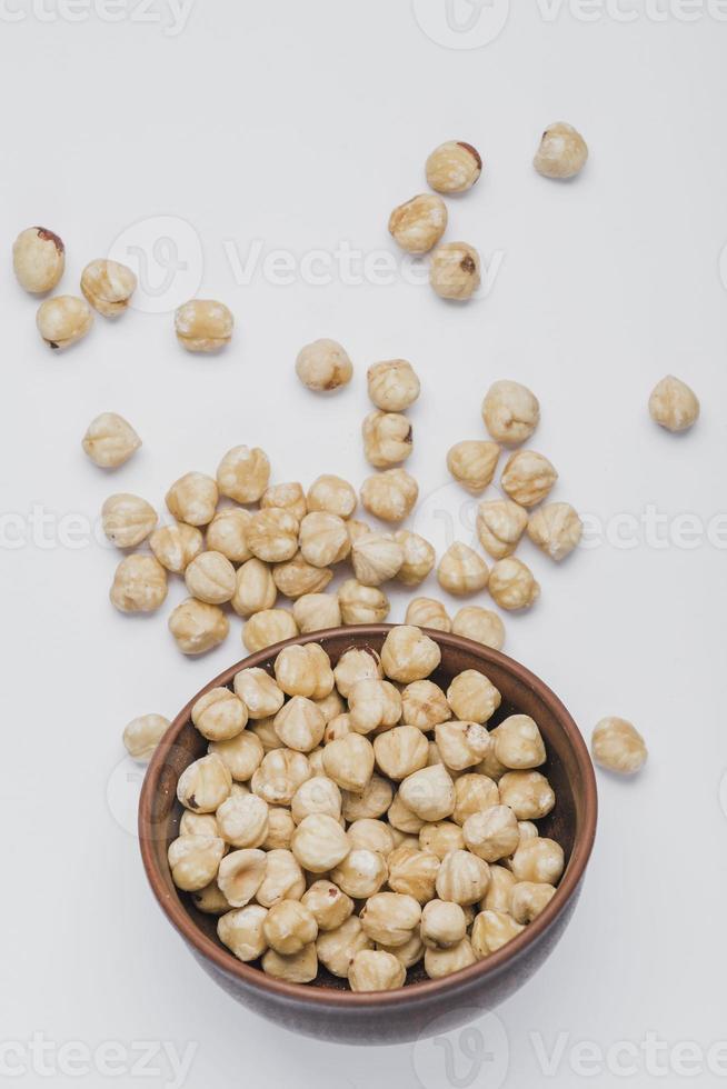 hasselnötter spillt nära skål på vit bakgrund foto