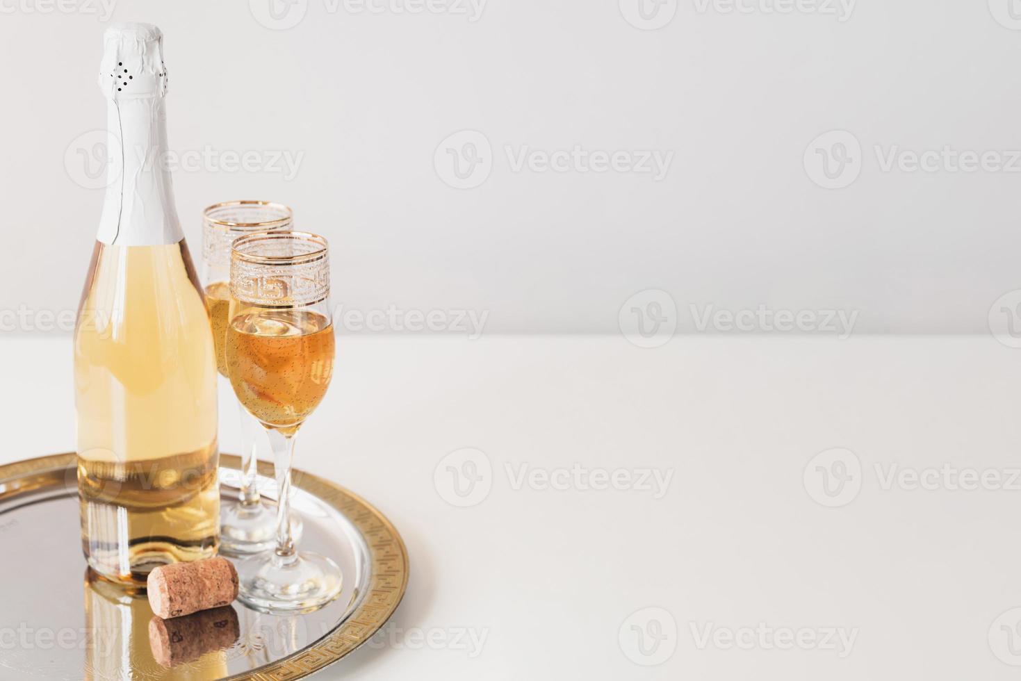 flaska med champagne och glas på bricka foto