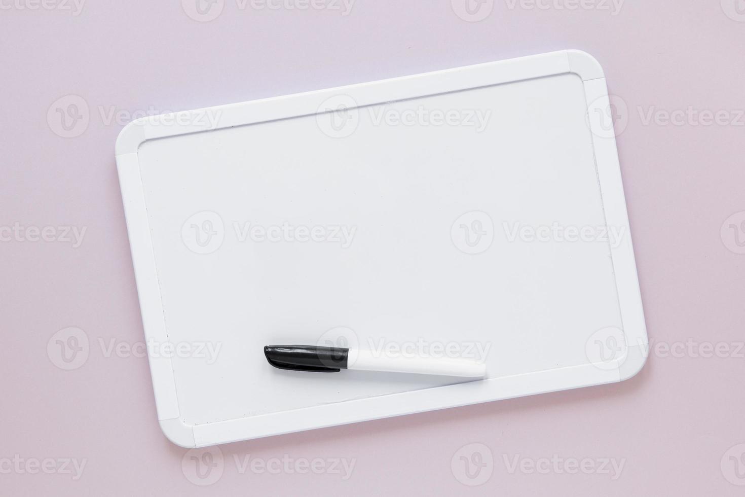 platt låg whiteboard med markeringstopp på ljusrosa bakgrund foto