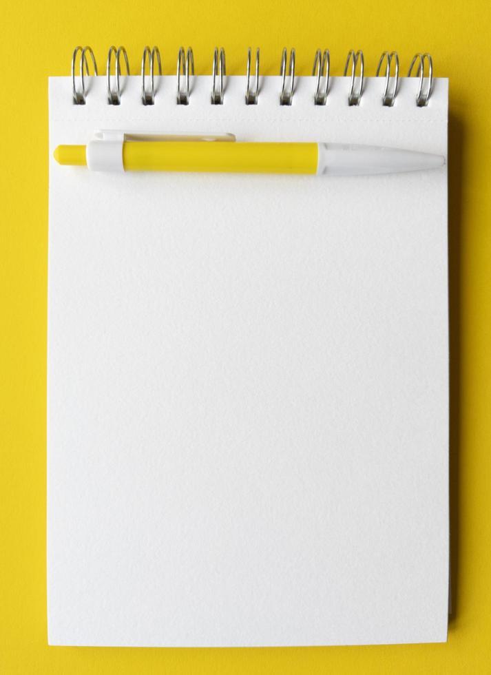 tomt ark anteckningsbok med penna på den. utbildningskoncept i gula och vita färger. stock photography. foto
