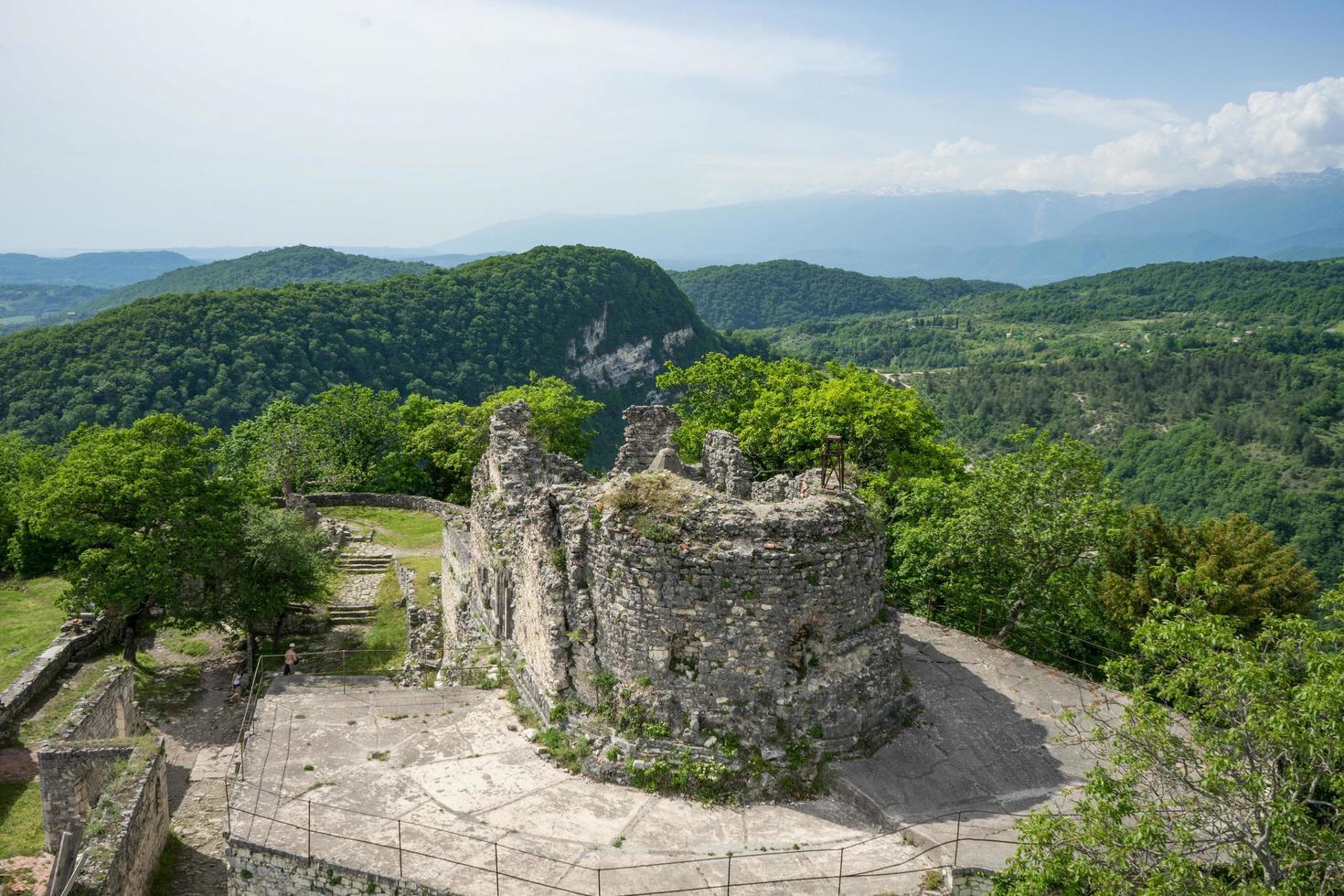 del av anakopifästningen med utsikt över den gröna skogen och bergen med en klarblå himmel i nya Aten, Abchazien foto