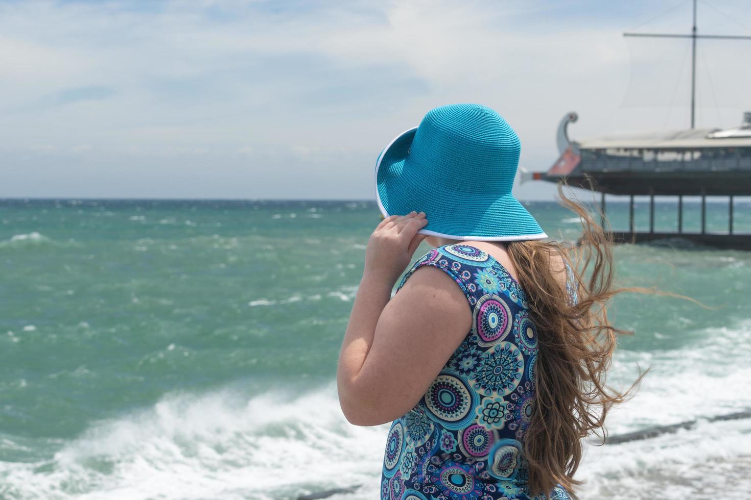en flicka i en blå hatt och färgglad klänning på en strand som tittar ut mot havet i Yalta, Krim foto