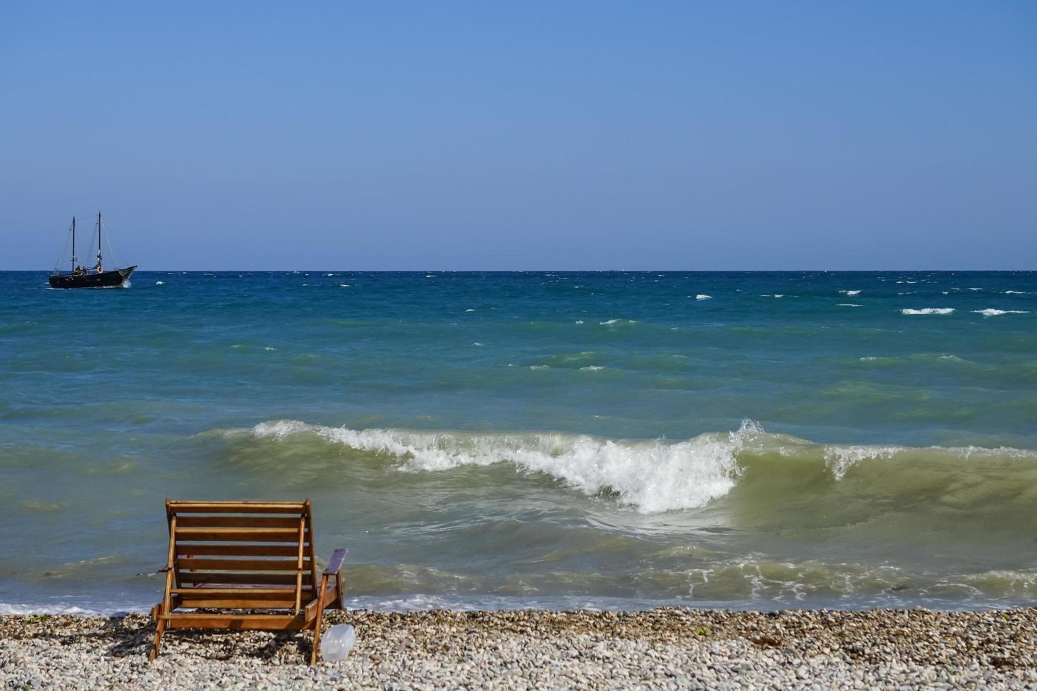marinmålning med en träbänk och ett skepp i horisonten. foto