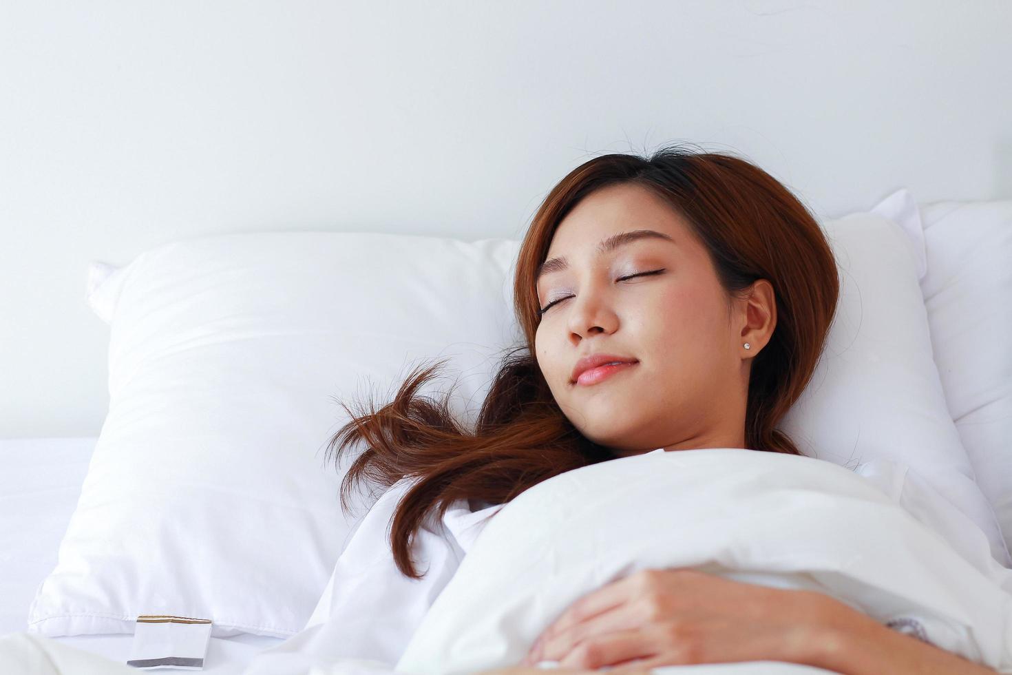 asiatisk kvinna sover i en vit säng på en semester hemma. foto