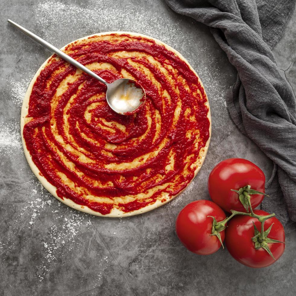 tomatsås på pizzadeg foto
