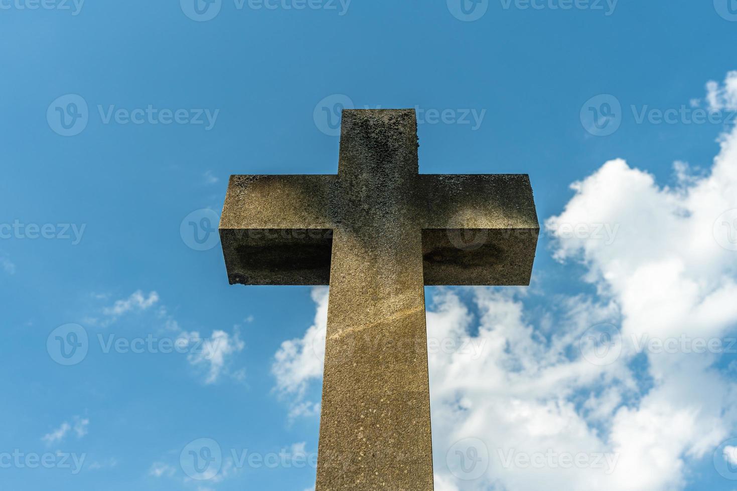 stort kors symbol gjord av sten mot en blå himmel foto