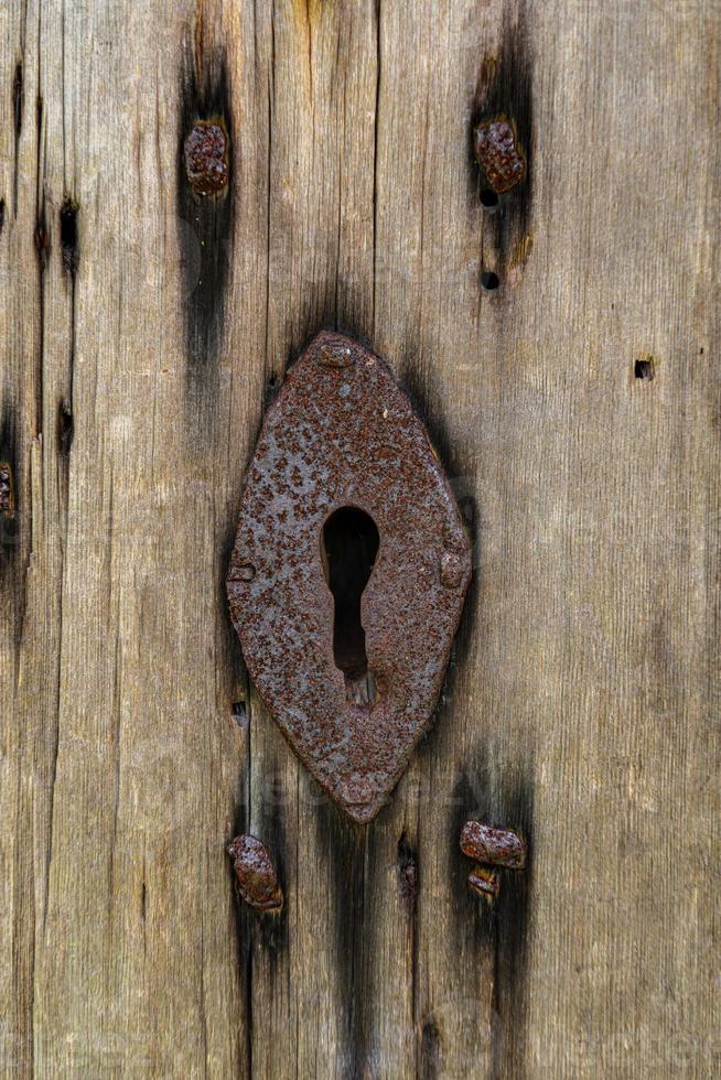 gammalt rostigt nyckelhål i en gammal trädörr foto