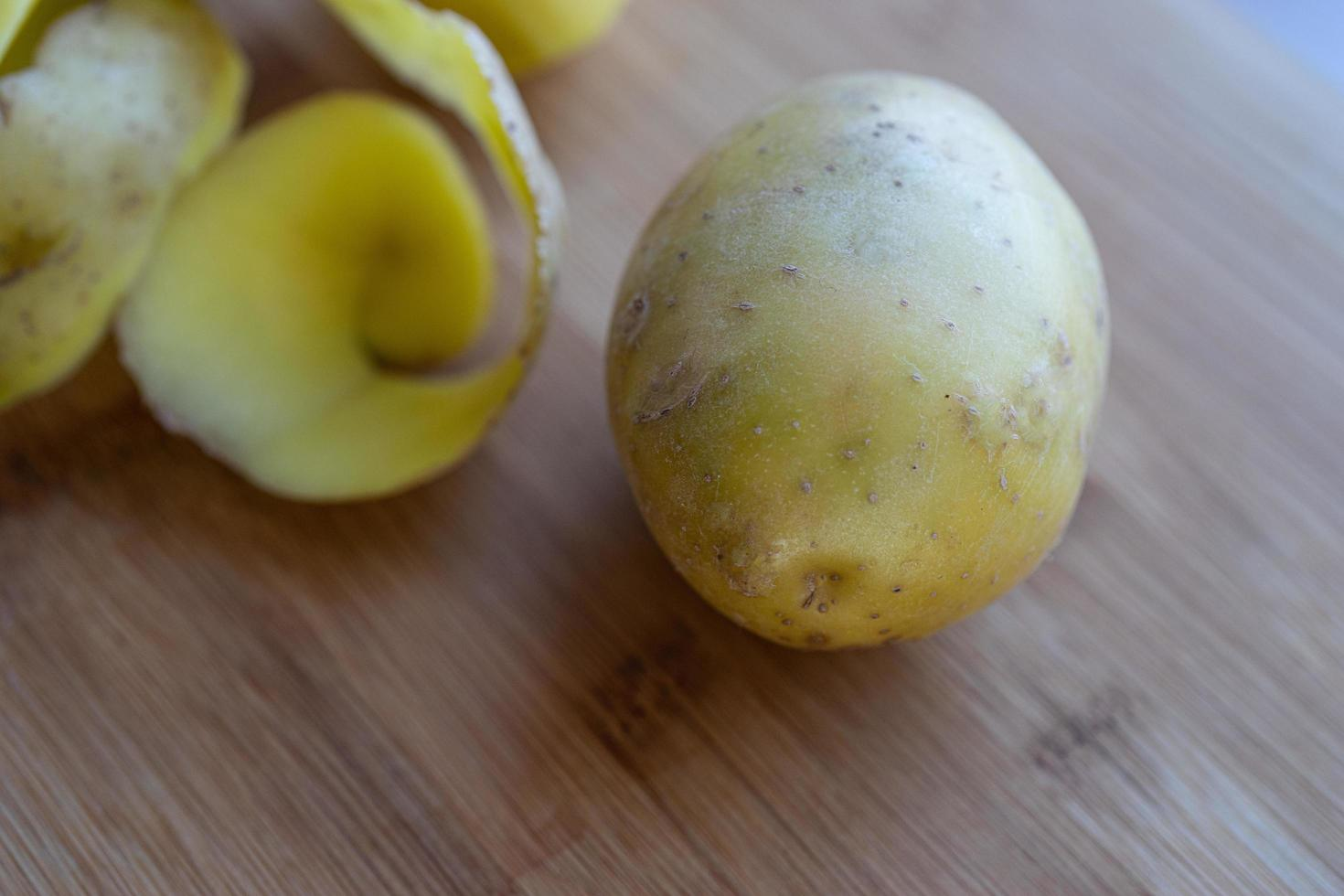 rå potatis med skal på en skärbräda foto