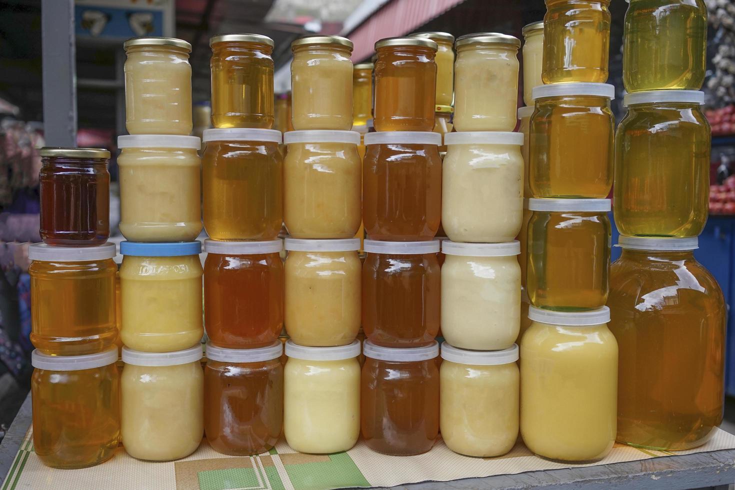 honung av olika färg i banker på en disk till salu. foto