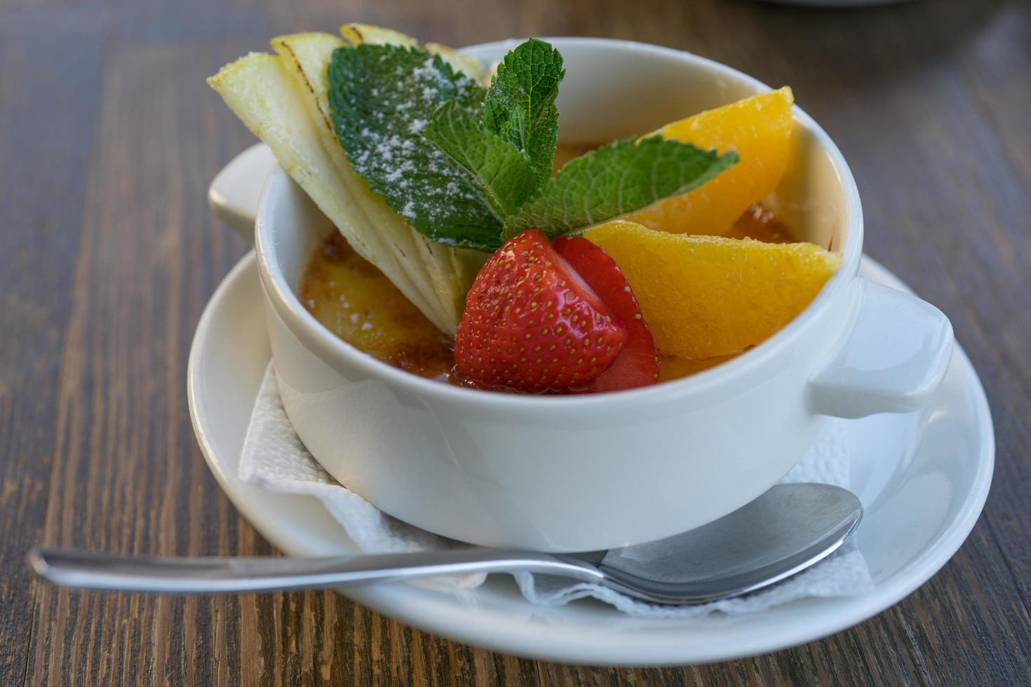karamell efterrätt med färska frukter i en snövit porslinskopp. foto