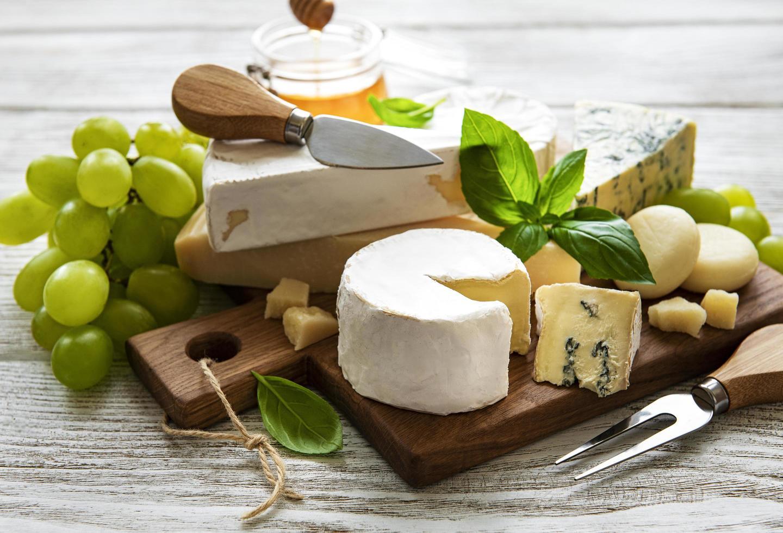 olika typer av ost på en vit trä bakgrund foto