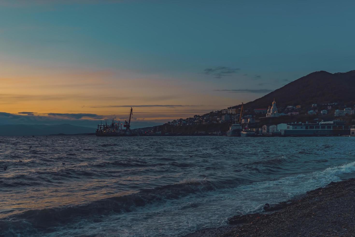 marinmålning med utsikt över solnedgången och kusten. foto