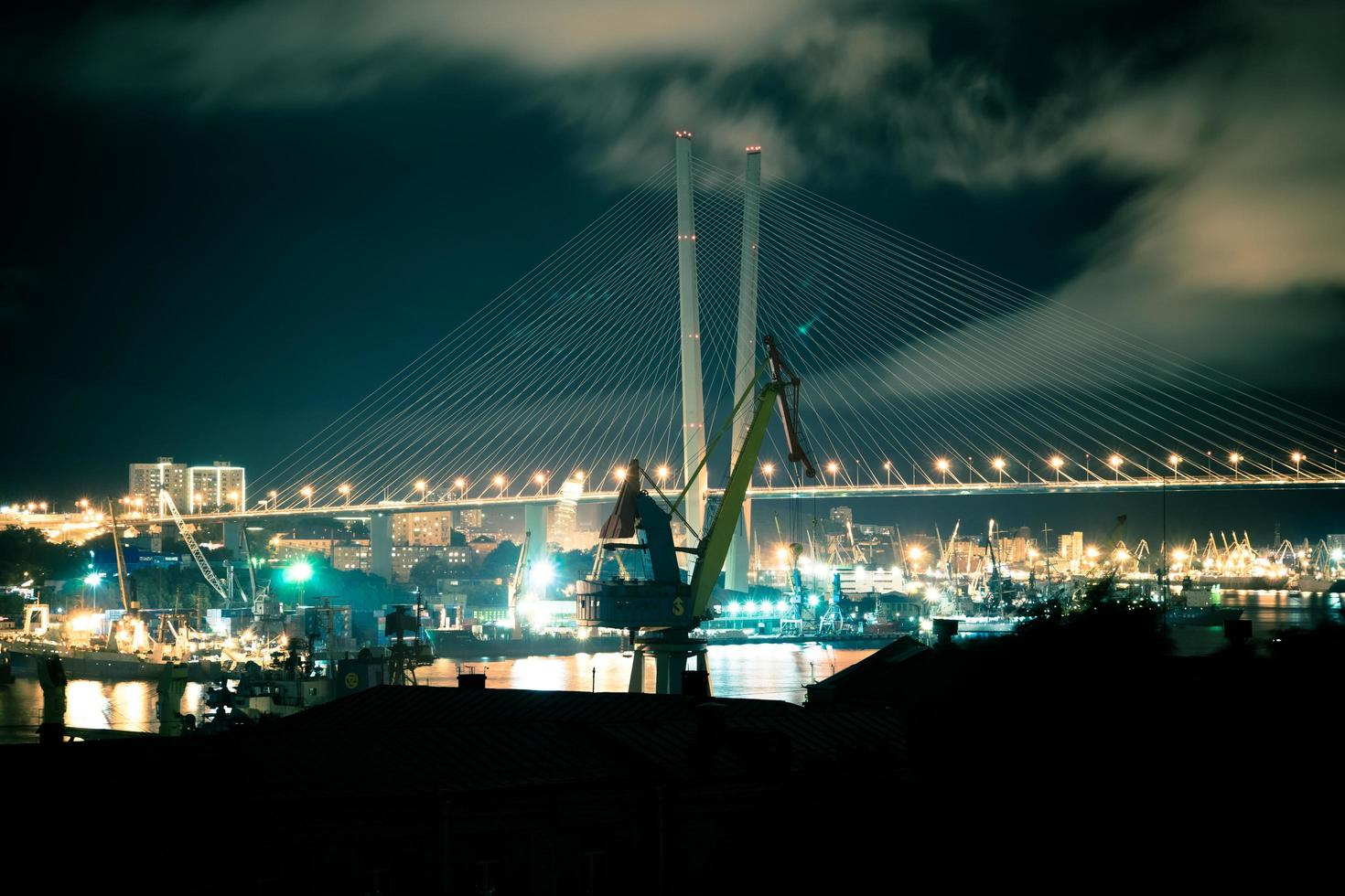 nattlandskap med kranar på bakgrunden av den gyllene bron. foto