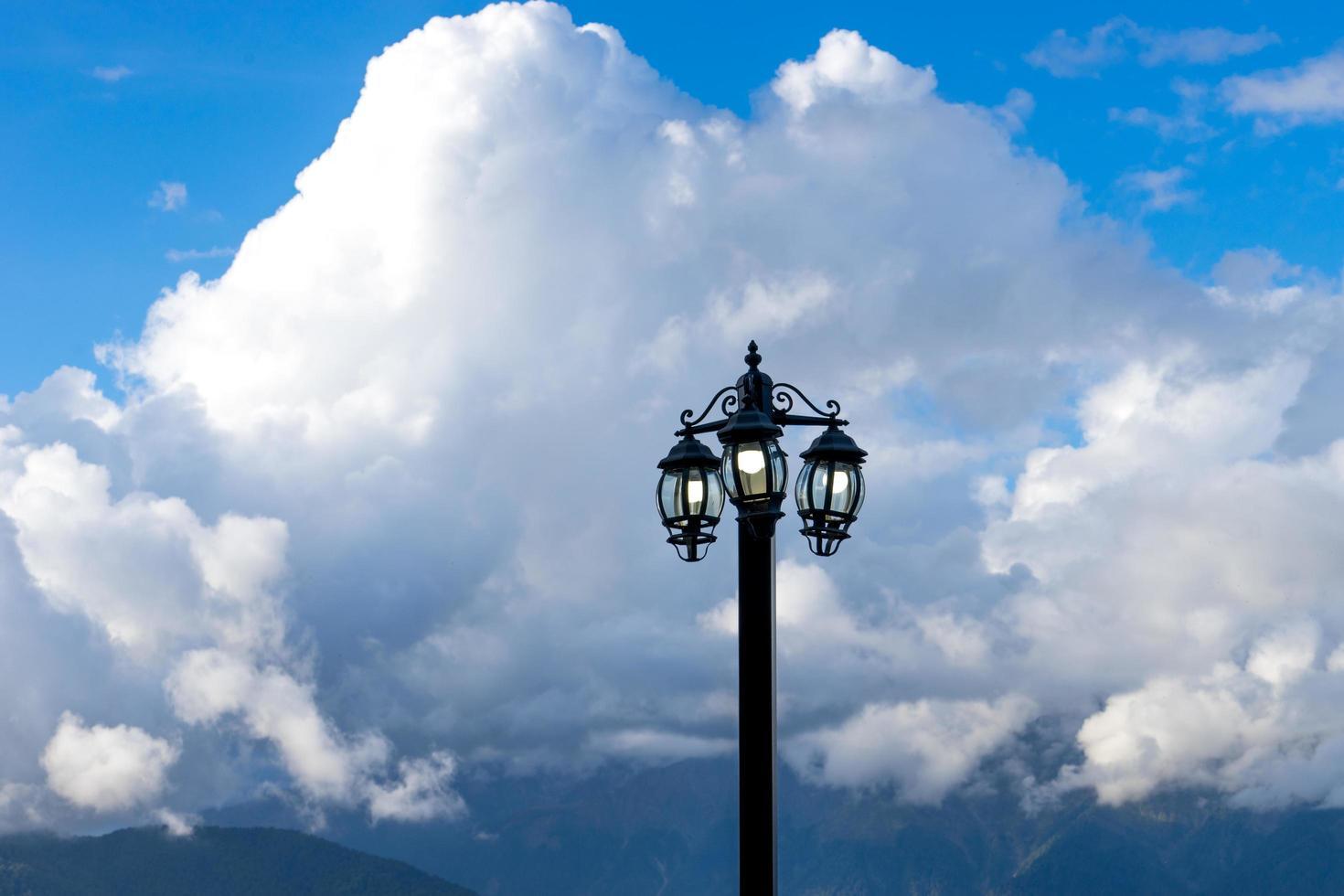 elektrisk fackla mot ett berglandskap och moln foto