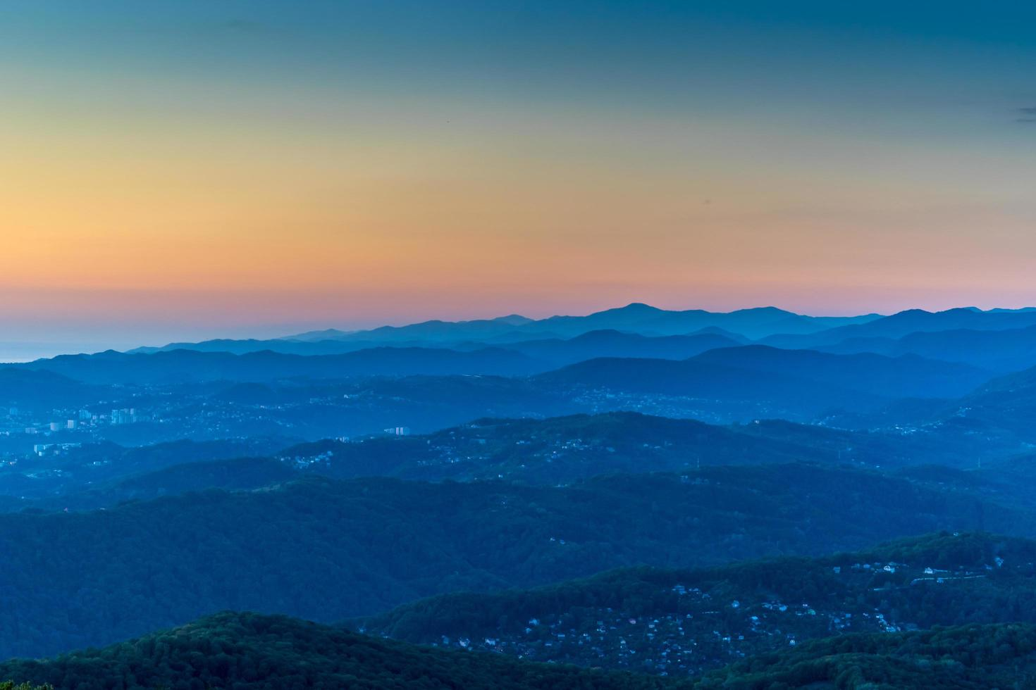 bergslandskap med flera rader av kullar vid solnedgången. foto