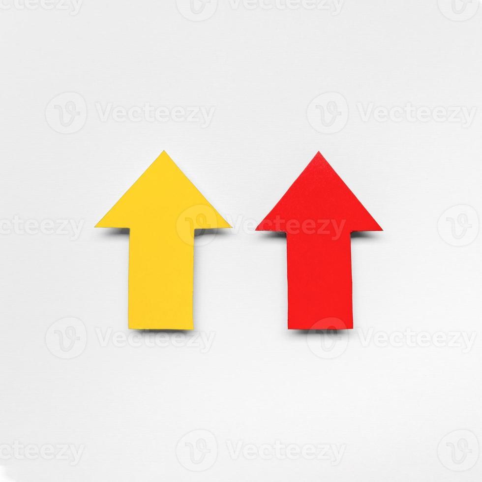 röda och gula pilskyltar pekar uppåt foto