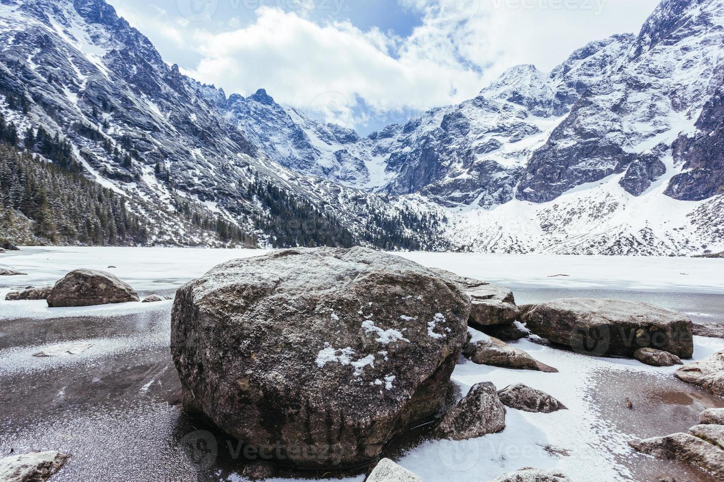 stenar nära en sjö med berg på vintern foto