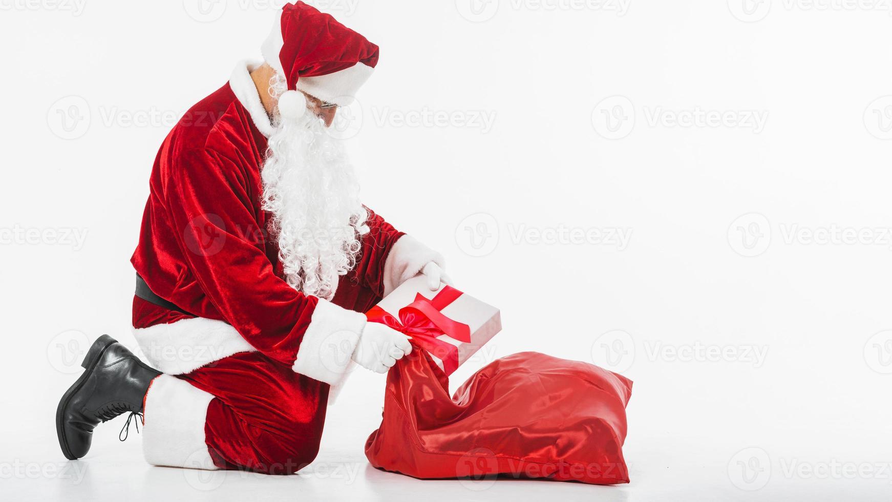 jultomten lägger presentask i säck foto