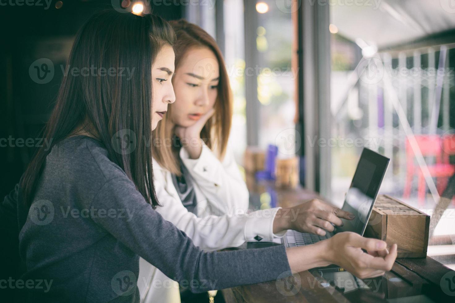 två asiatiska affärskvinnor som arbetar på en bärbar dator foto