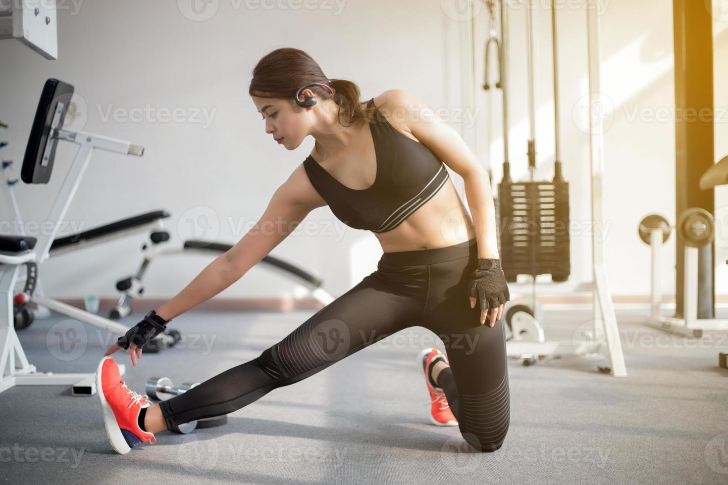 kvinna som sträcker sig i gymmet foto