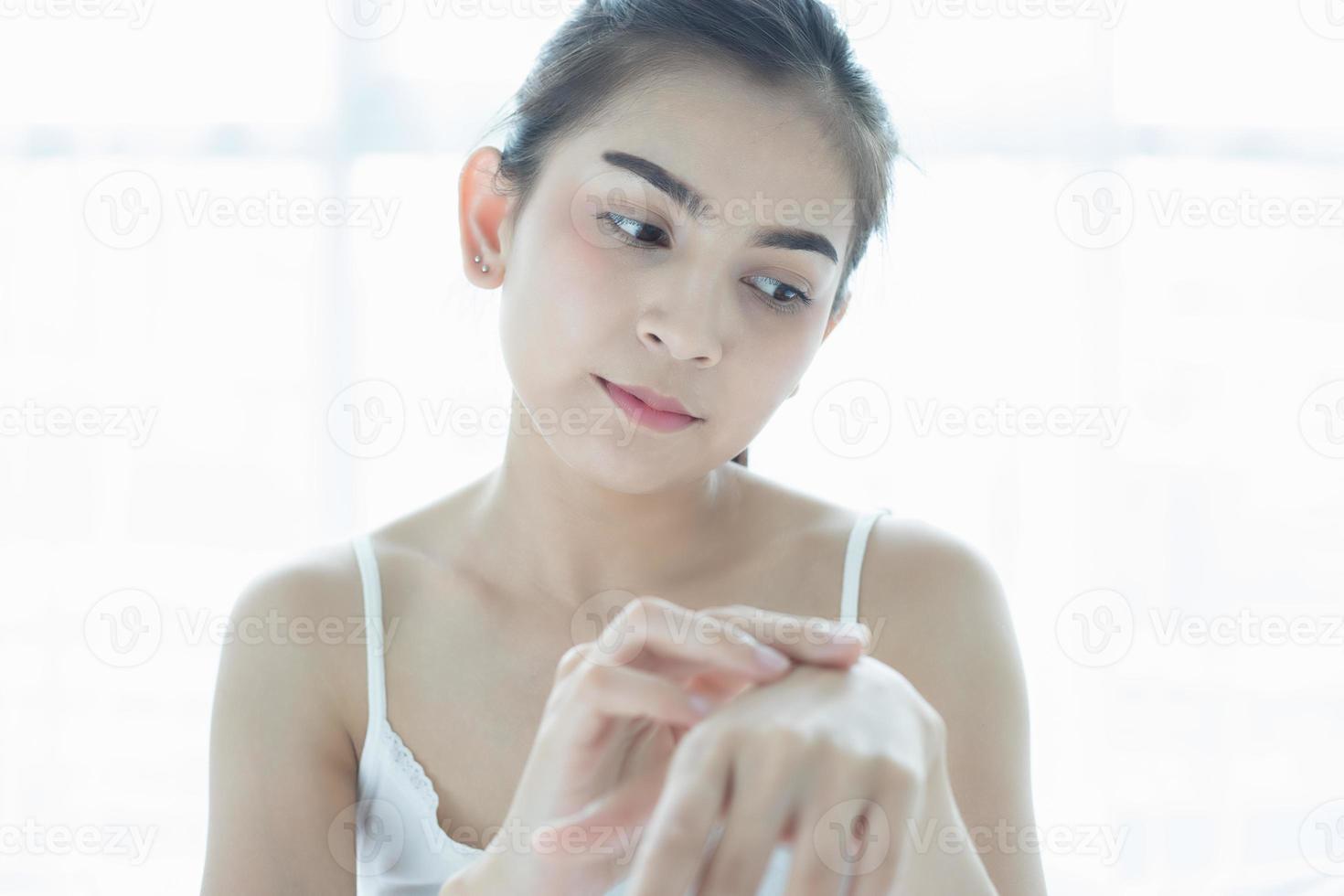 asiatisk kvinna återfuktar huden foto
