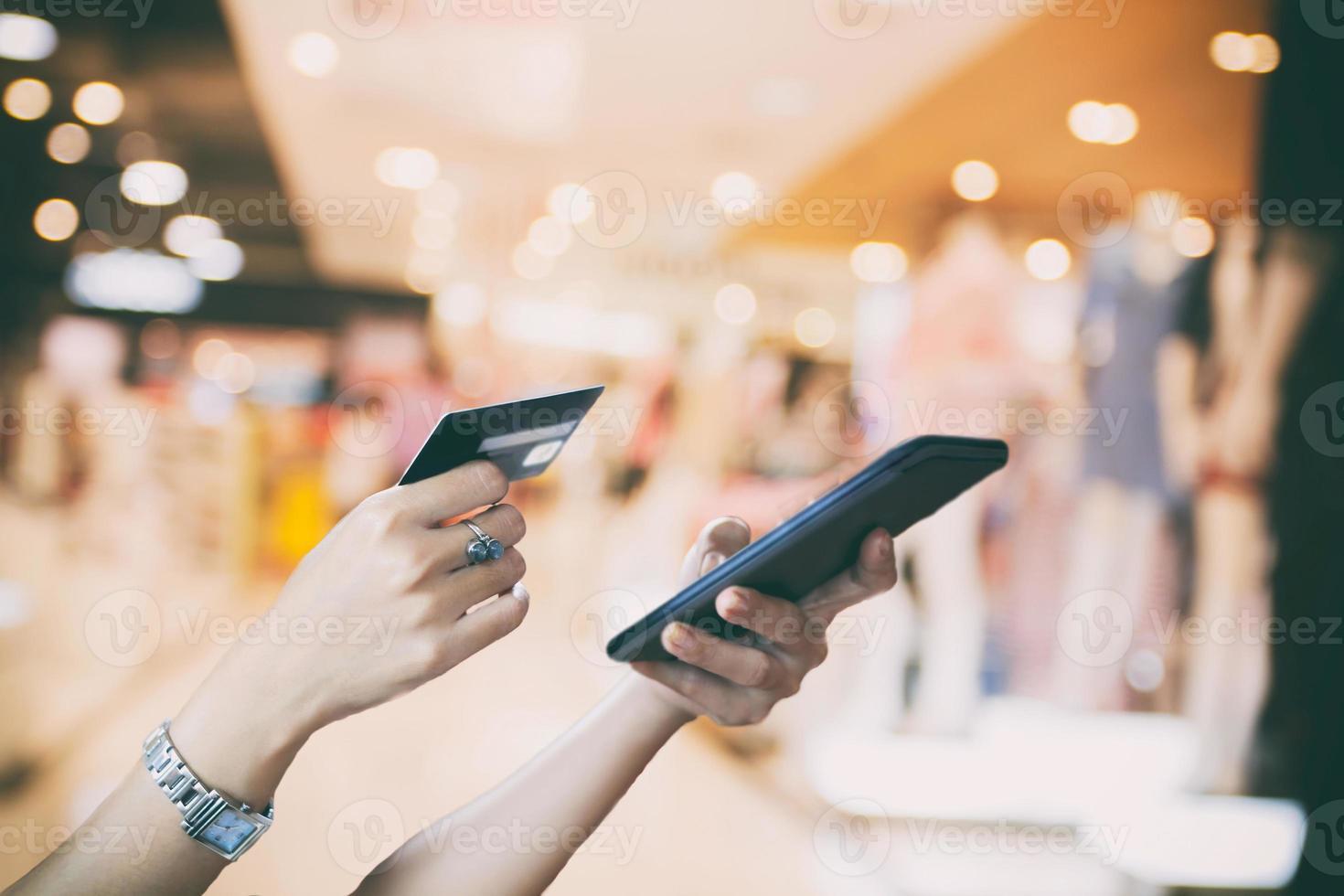 asiatisk kvinna som använder smart telefon och kreditkort för att betala foto