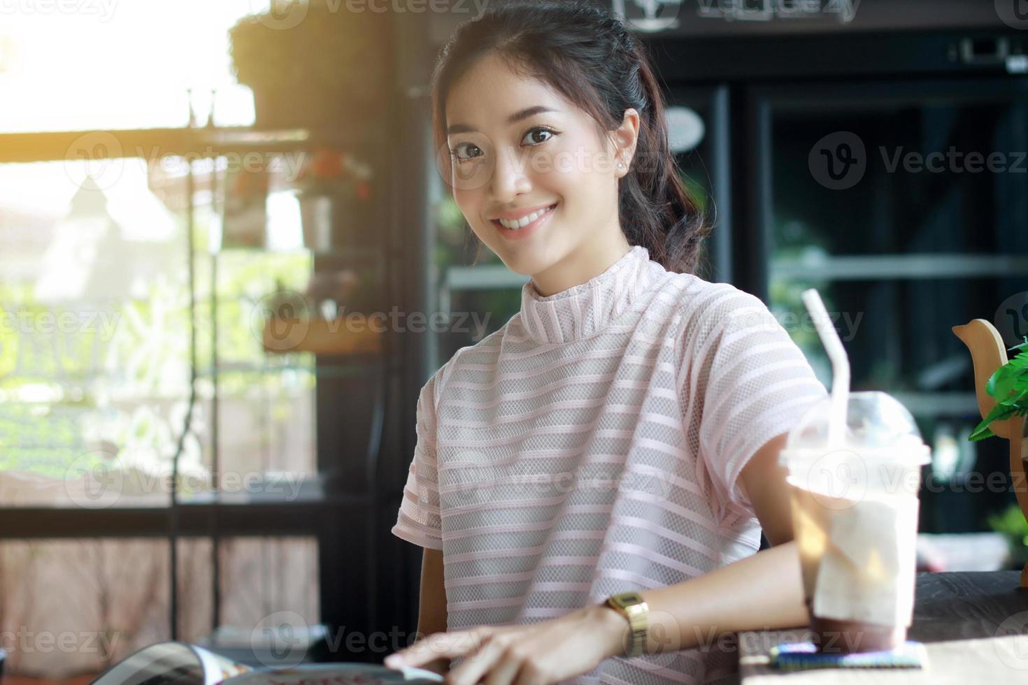 asiatisk kvinna som läser en bok för avkoppling på kaffekaféet foto