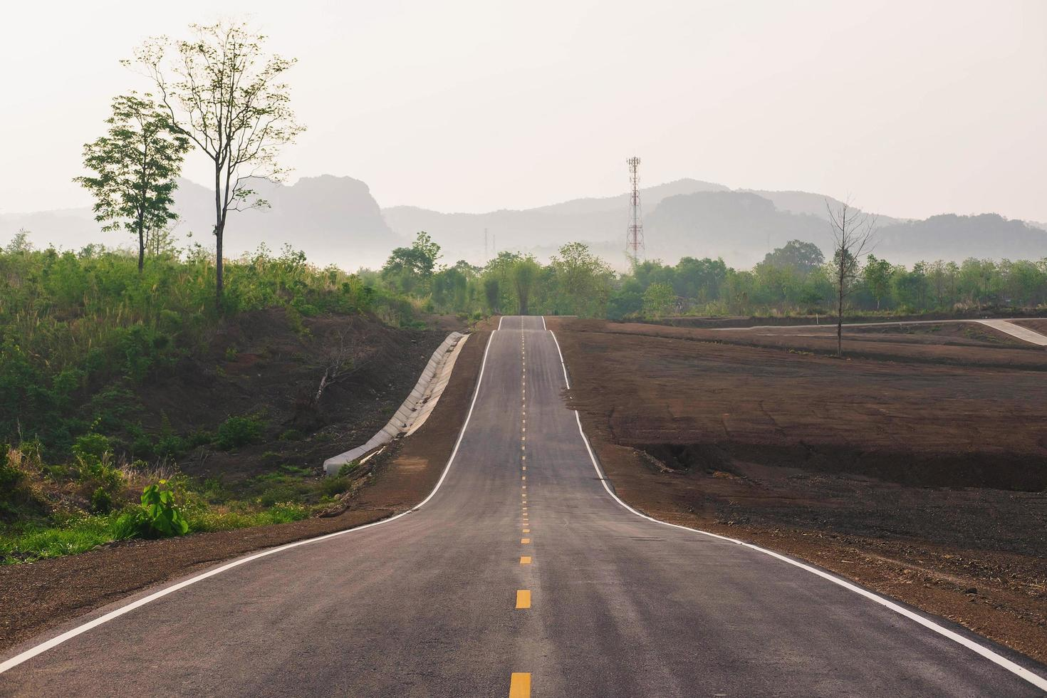 en lång rak väg som leder mot ett berg foto