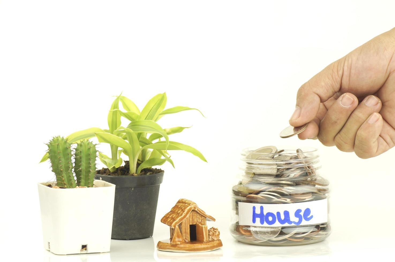 hand sätta mynt på en flaska pengar för huset foto