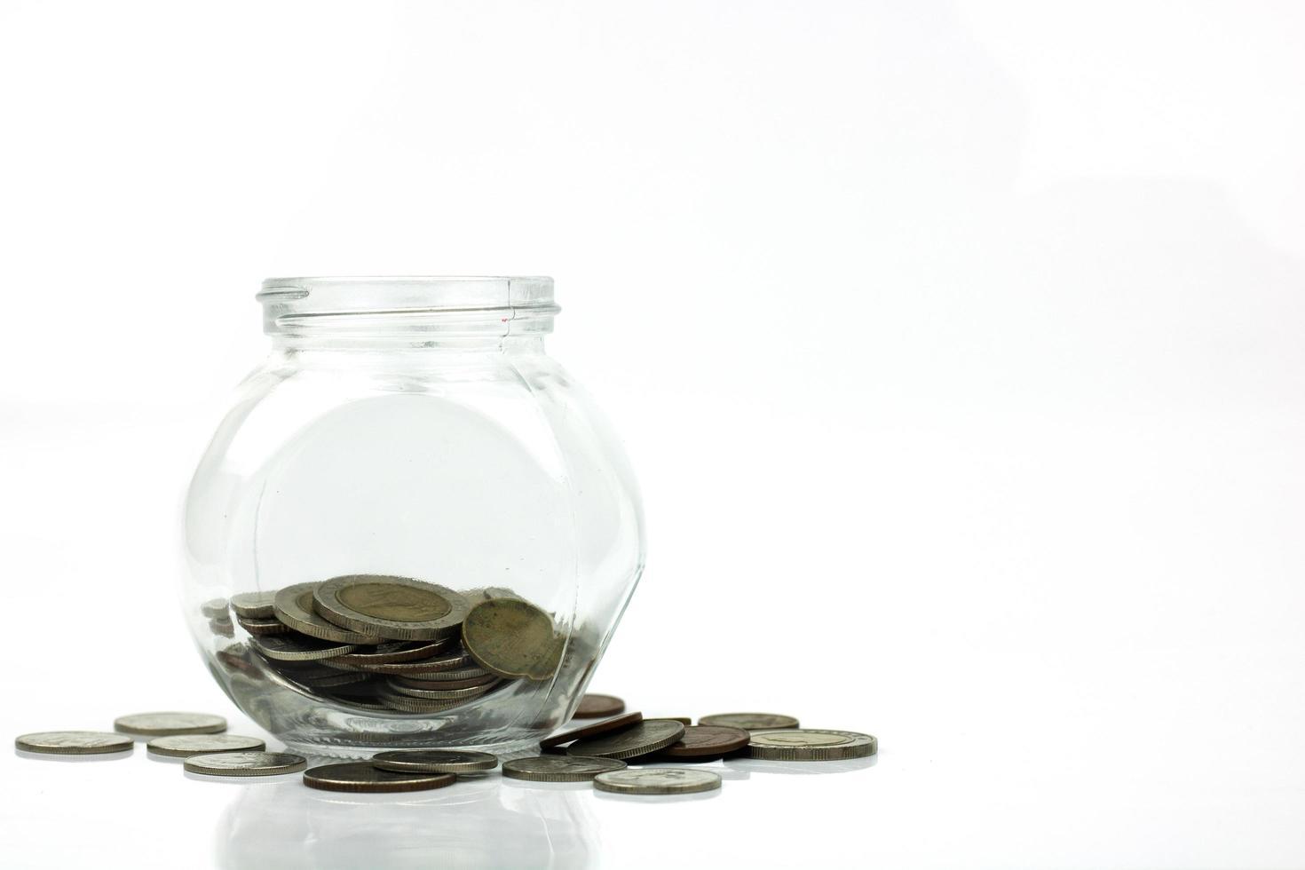 spara pengar och investeringskonceptmynt som växer upp i glas isolerad på vit bakgrund foto