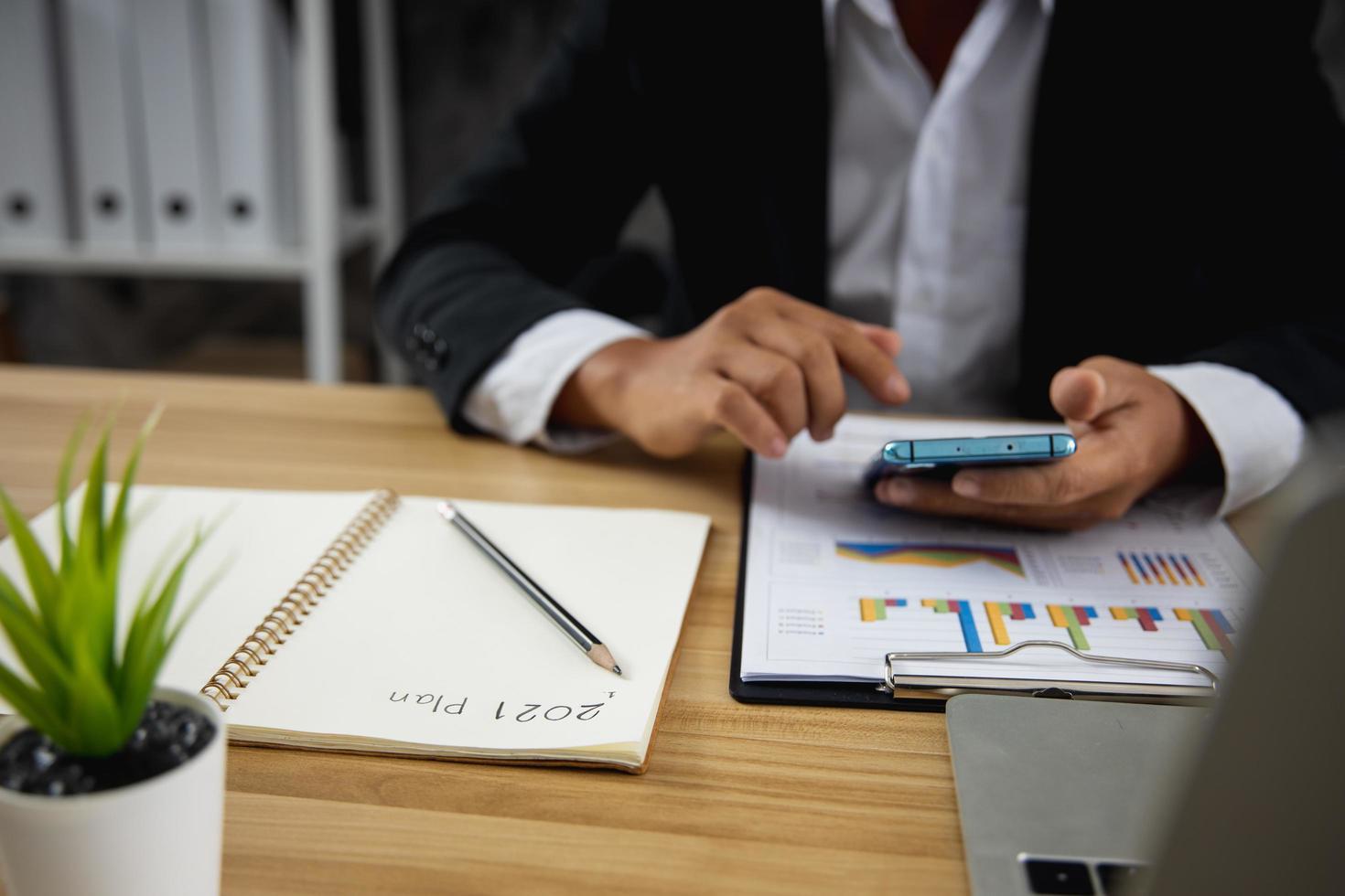 affärsman som letar efter telefon för beslutade och planerar jobb på papper 2021 foto