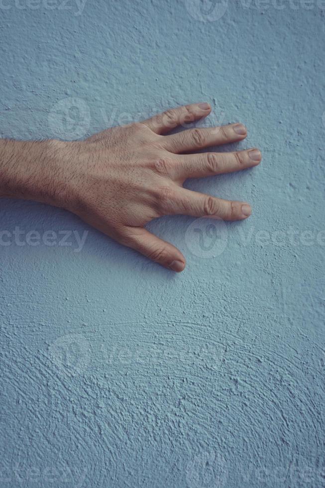 hand som gester på den blå väggen foto