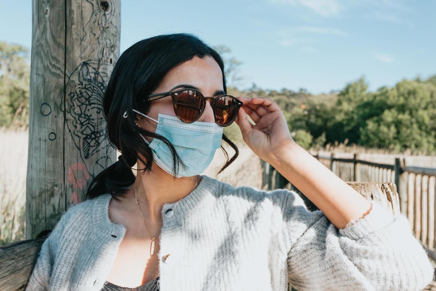 kvinna som använder solglasögon och en ansiktsmask foto