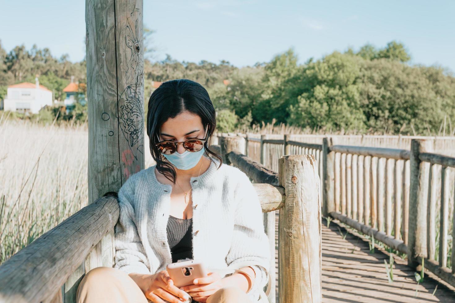 ung kvinna som använder solglasögon och en ansiktsmask medan du använder en telefon foto
